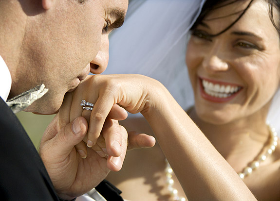 Caucasian prime adult male groom kissing hand of female bride.